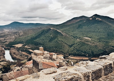 aerial photography of brown buildings and green mountain during daytime spain zoom background