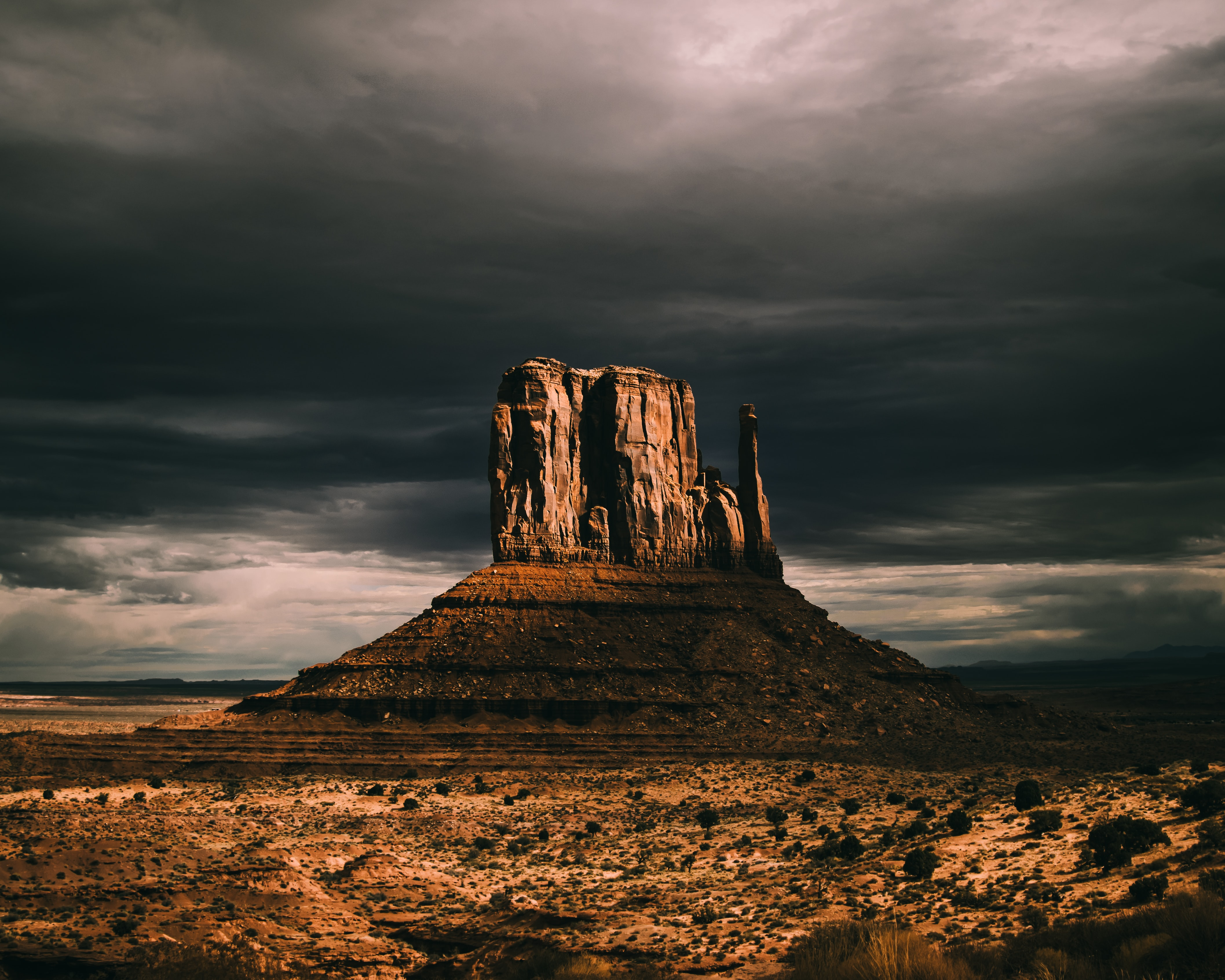 brown rock formation under cloudy sky