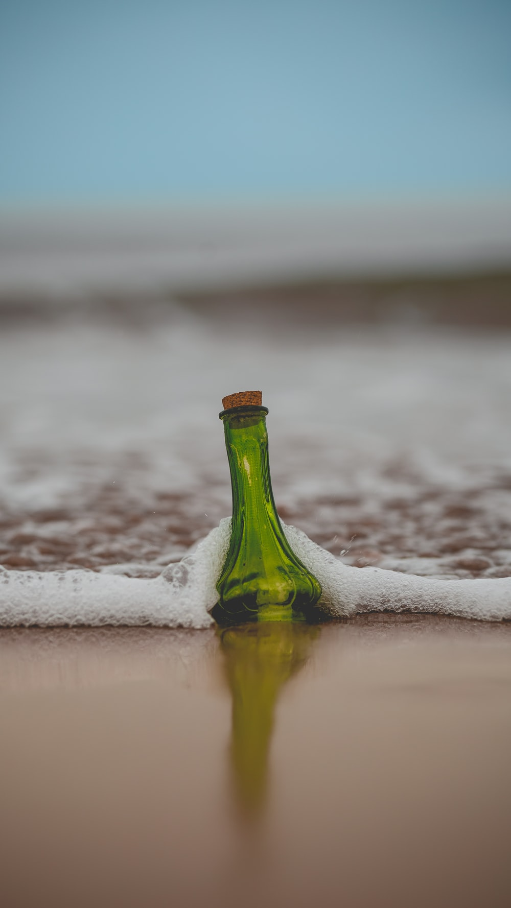 green glass bottle with cork lid on shore