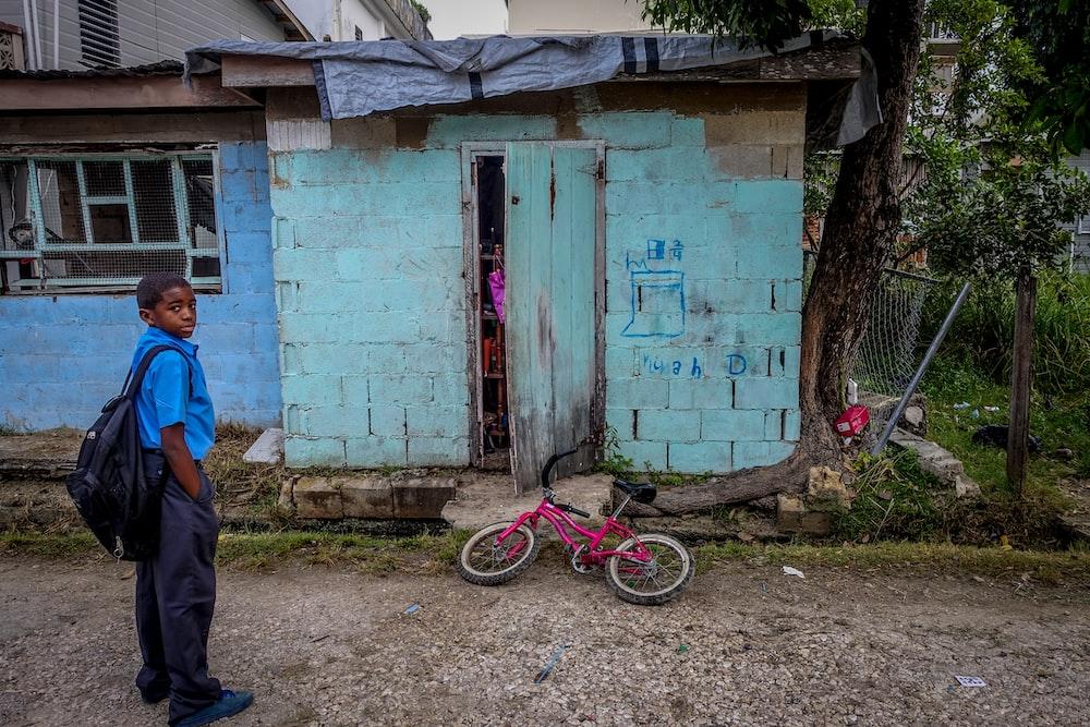 boy standing in front of door near bicycle