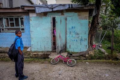boy standing in front of door near bicycle belize zoom background