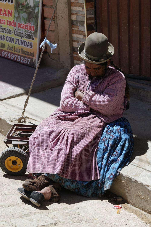 person sitting white sleeping on gray concrete street pathway during daytime
