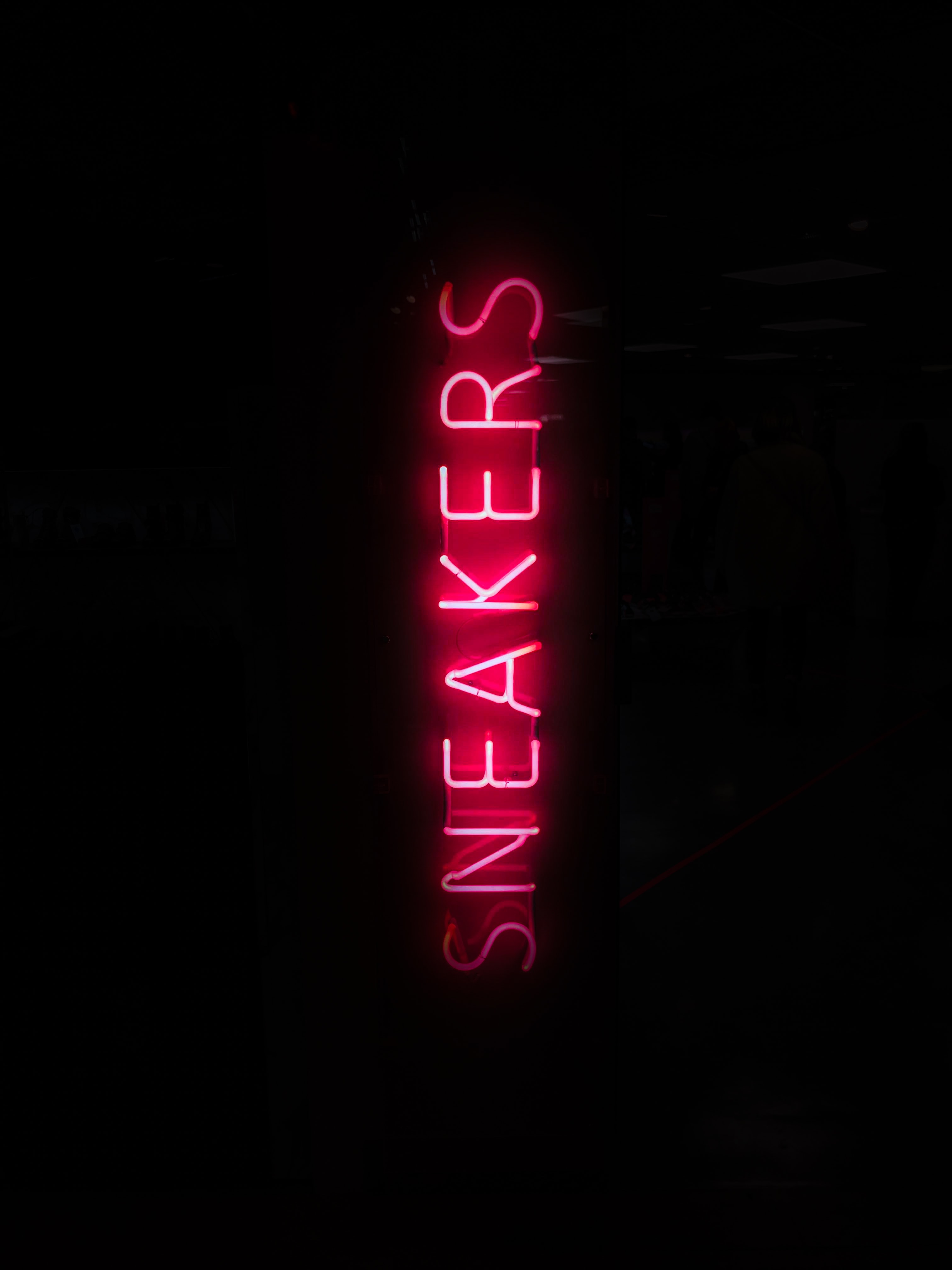 turned on red sneakers neon light in dark place