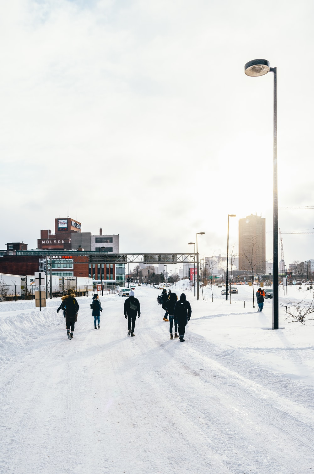 people walking on snow covered road during day time