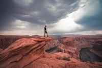 man standing on top of horseshoe bend at Arizona