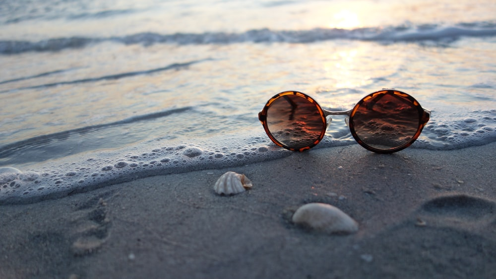 brown sunglasses on seashore