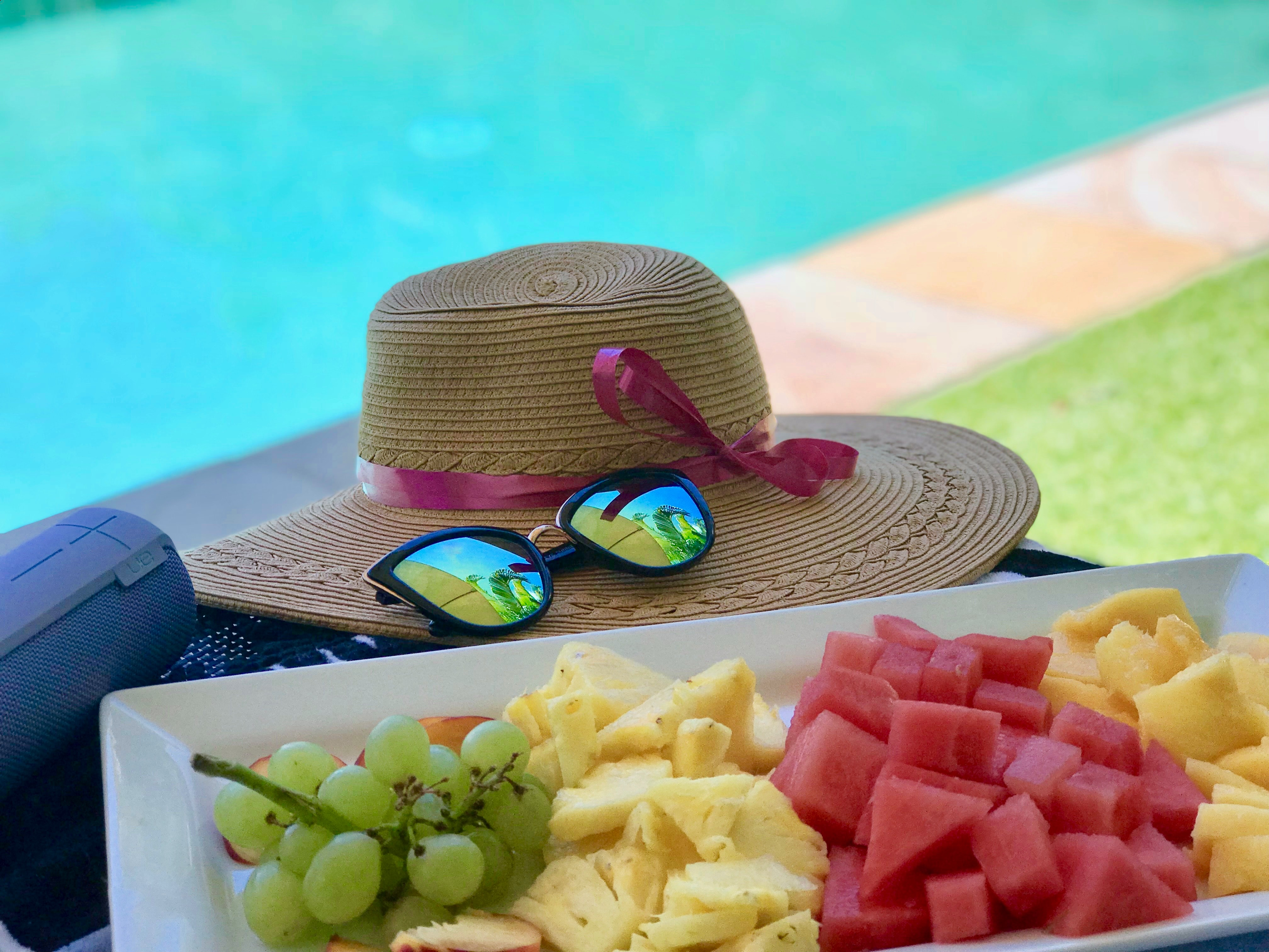 sliced fruits on white tray next to sunglasses and straw hat