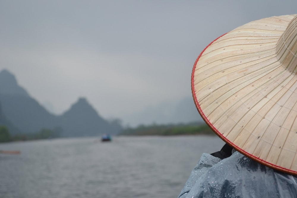 man wearing straw hat fronting body of water