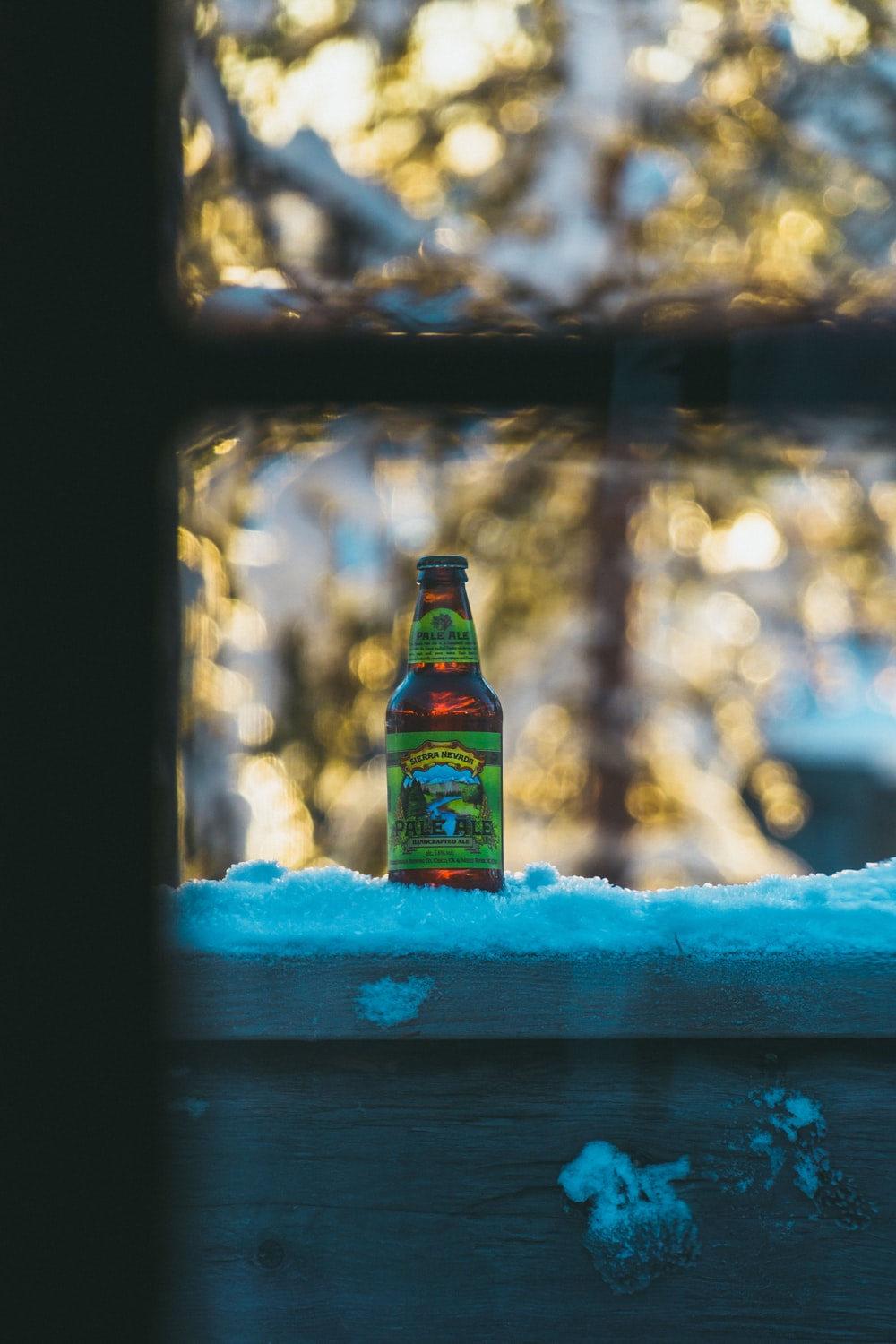 brown glass bottle on snow
