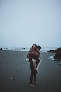 candid photography of man carrying woman at back near seashore