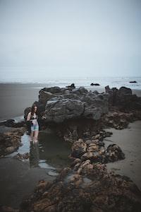 woman standing beside stone on beach shore