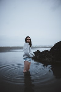 woman in gray sweater standing on shallow sea water under gray sky