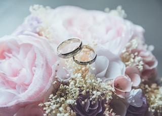 gold-colored bridal ring set on pink rose flower bouquet
