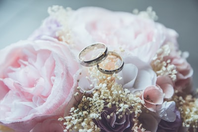 gold-colored bridal ring set on pink rose flower bouquet marriage zoom background