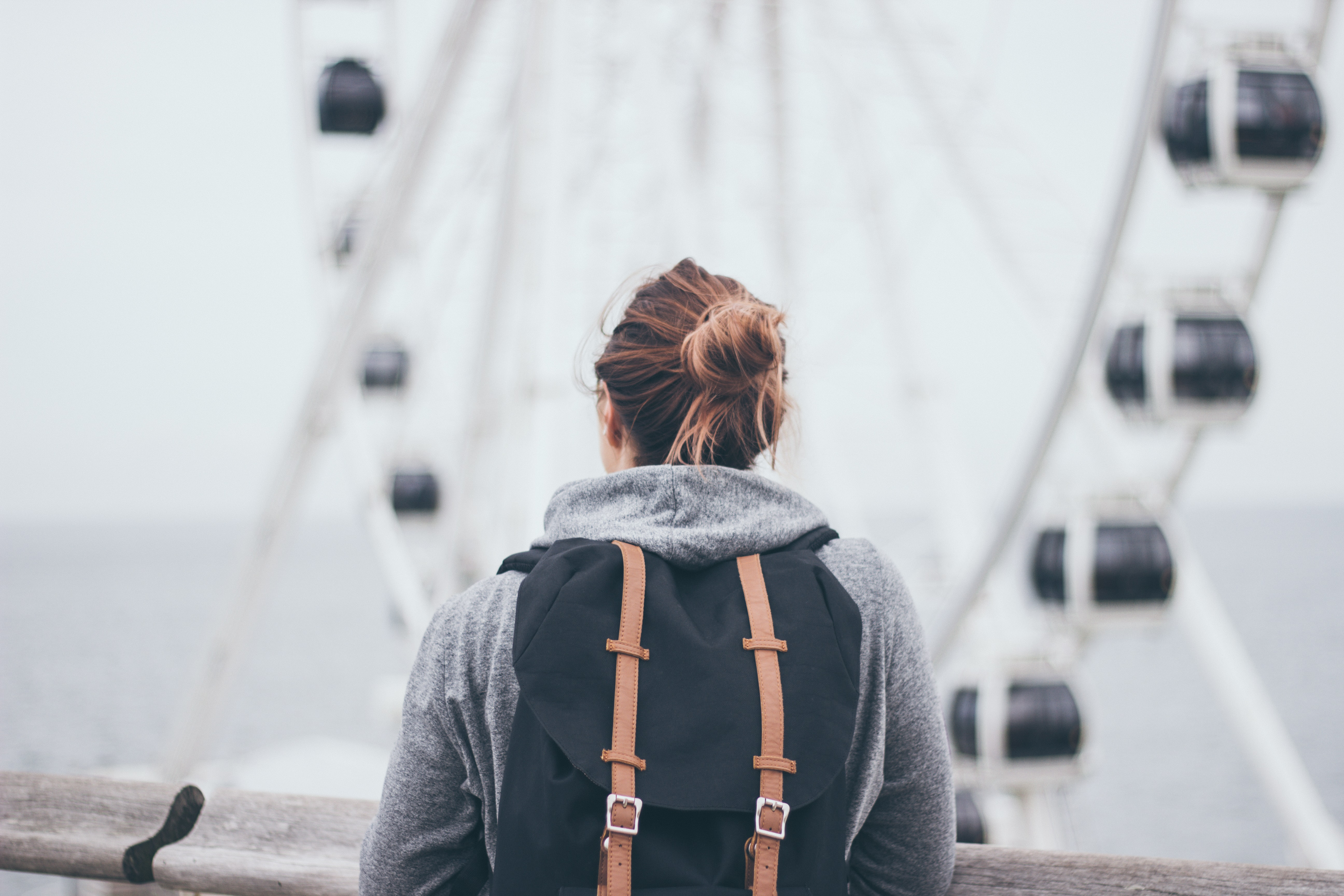 person carrying rucksack standing near rail