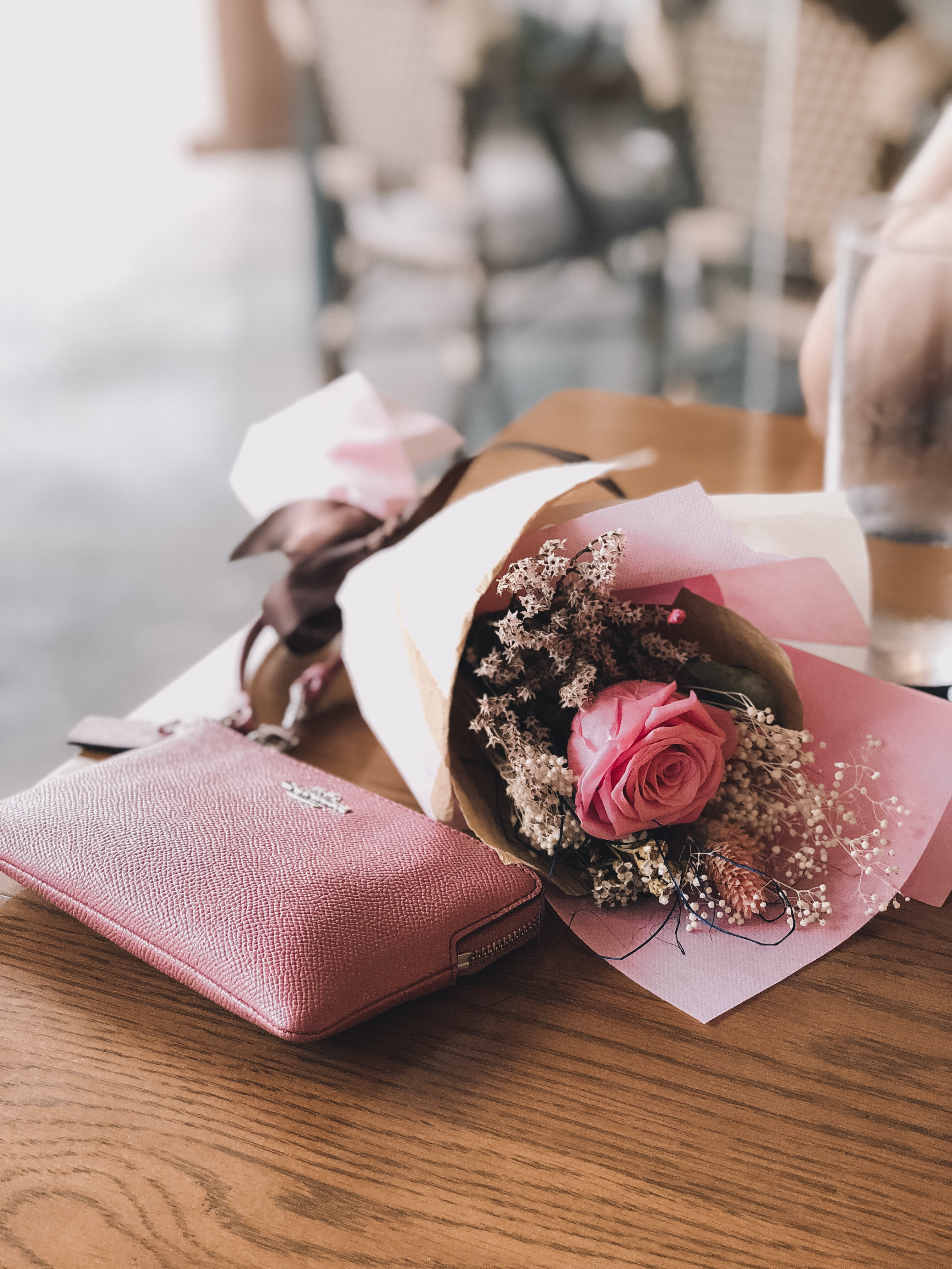pink rose flower near the pink Coach leather wallet on brown wooden table