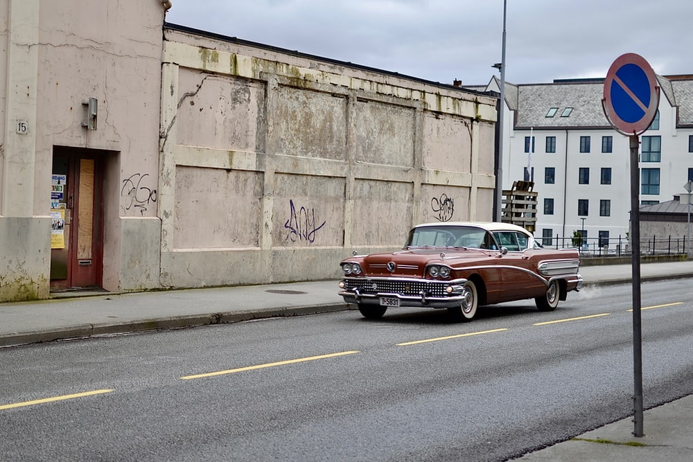 red Chevrolet Bel Air parked near brown building