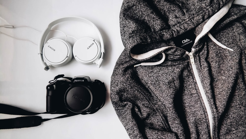 black DSLR camera and white Sony wireless headphones beside gray and white zip-up hooded jacket
