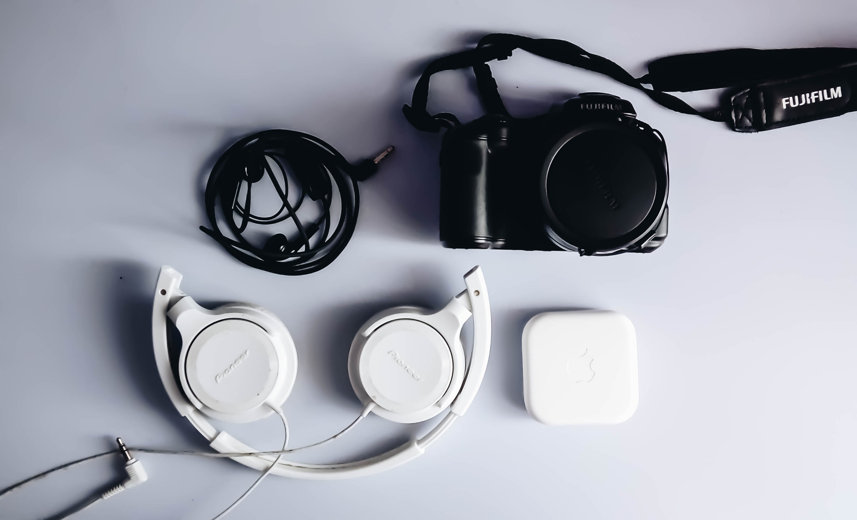 black Fujifilm DSLR camera and white corded headphones