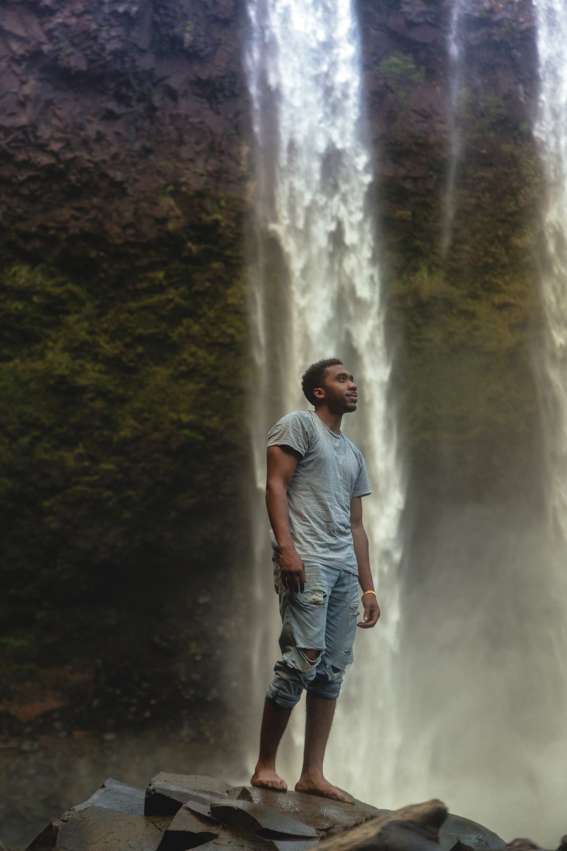 man standing near waterfall wearing gray crew-neck t-shirt and blue distressed denim pants