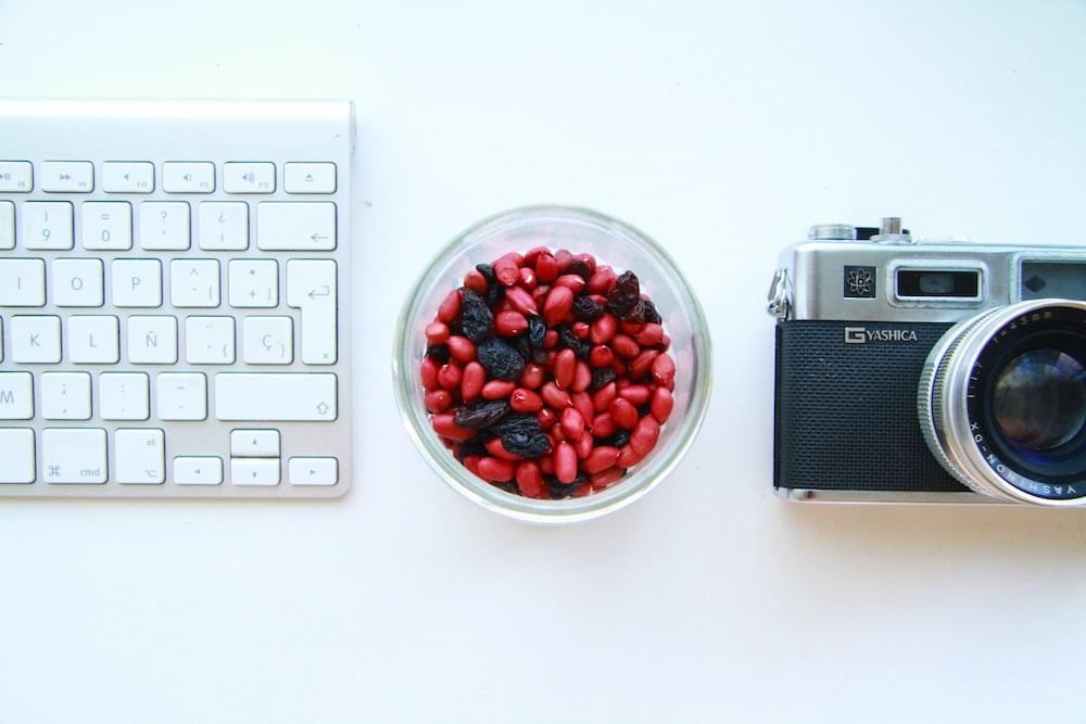 black and gray SLR camera and white keyboard