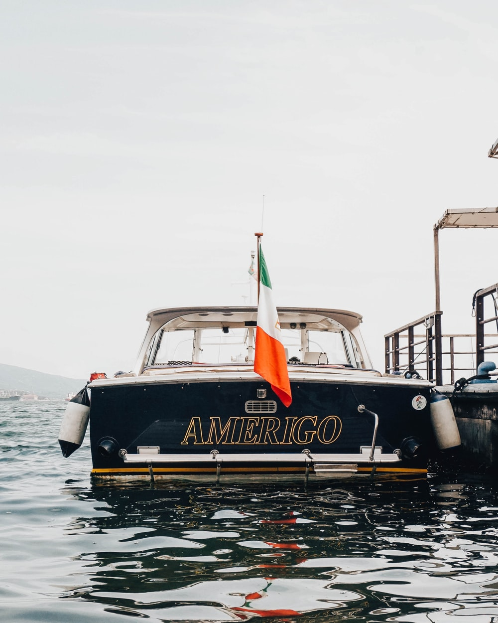 black and white Amerigo boat beside gray concrete dock during daytime