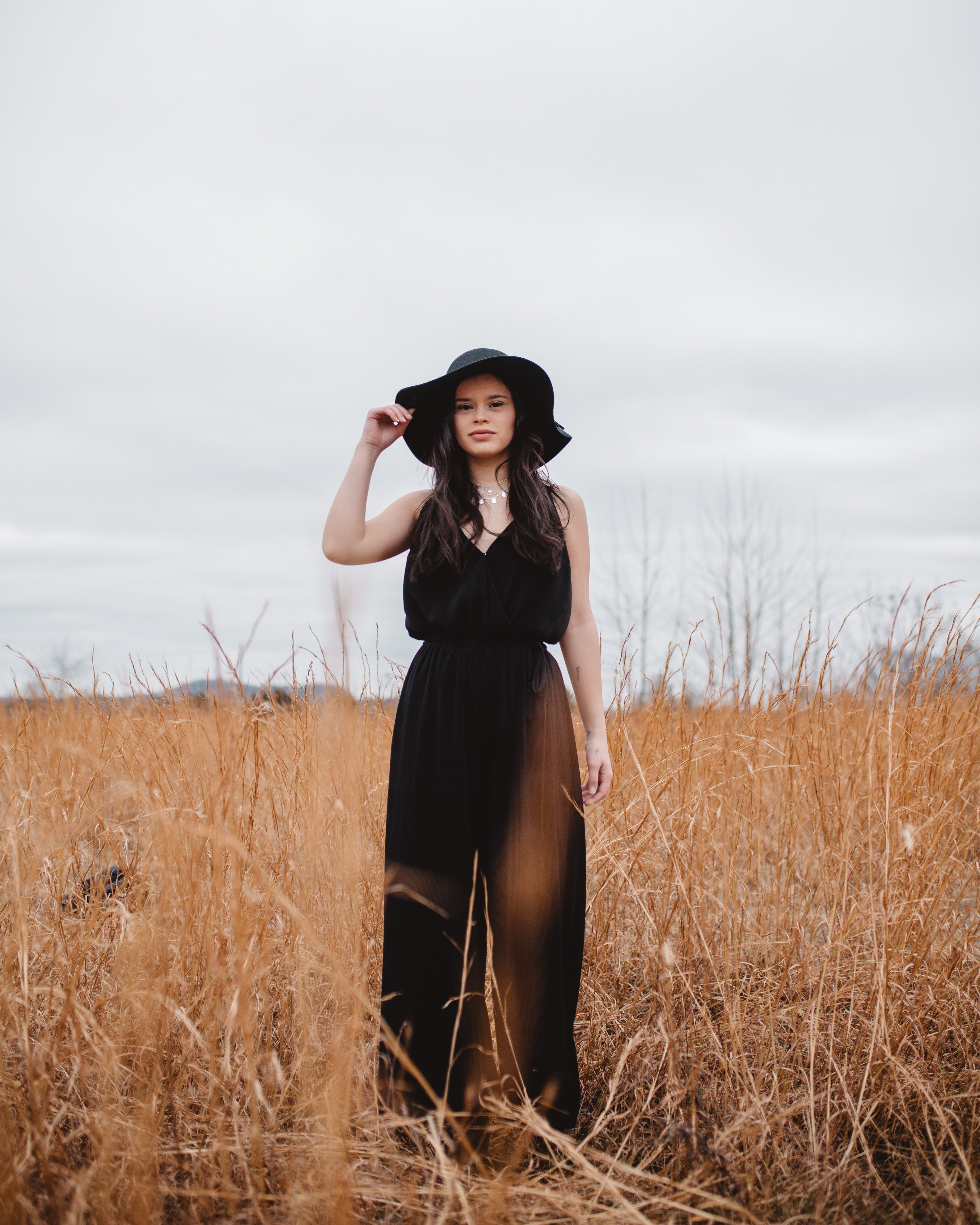 woman wearing black V-neck spaghetti-strap jumpsuit and black hat standing on brown grass field