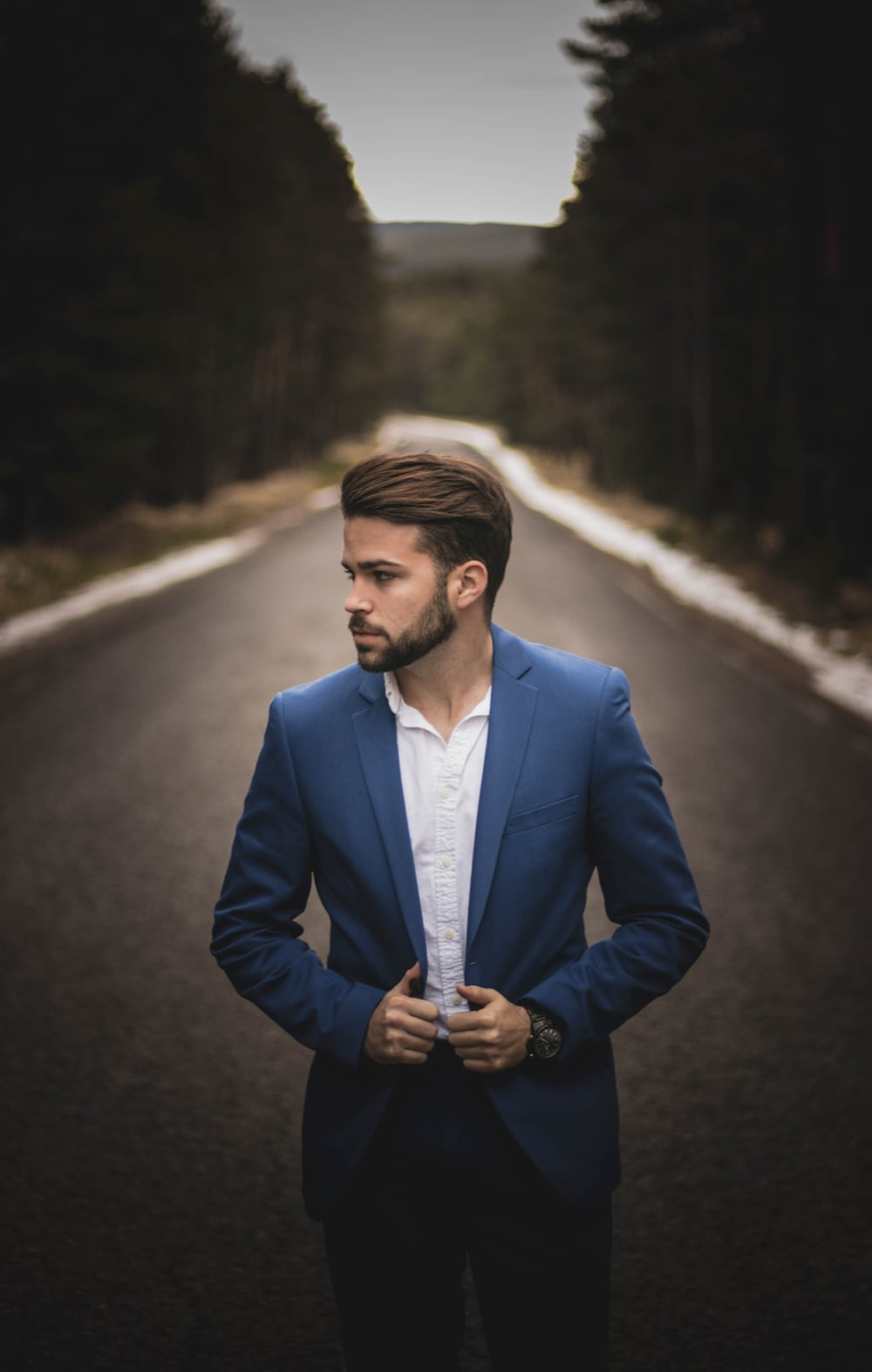 man on road wearing blue suit jacket