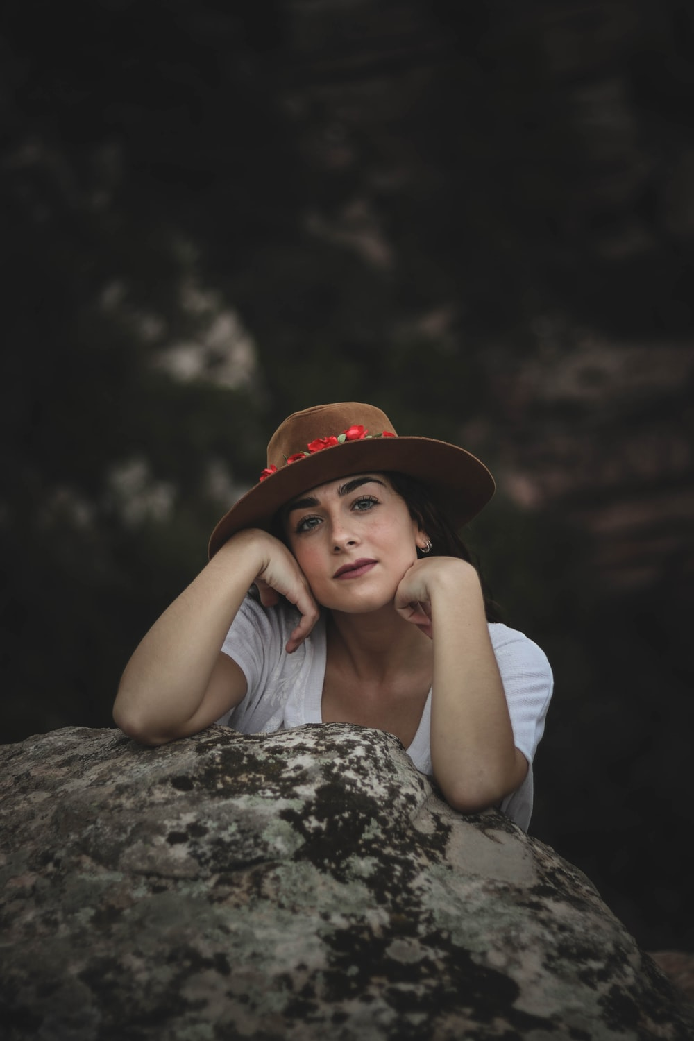 woman wearing hat leaning on gray rock formation