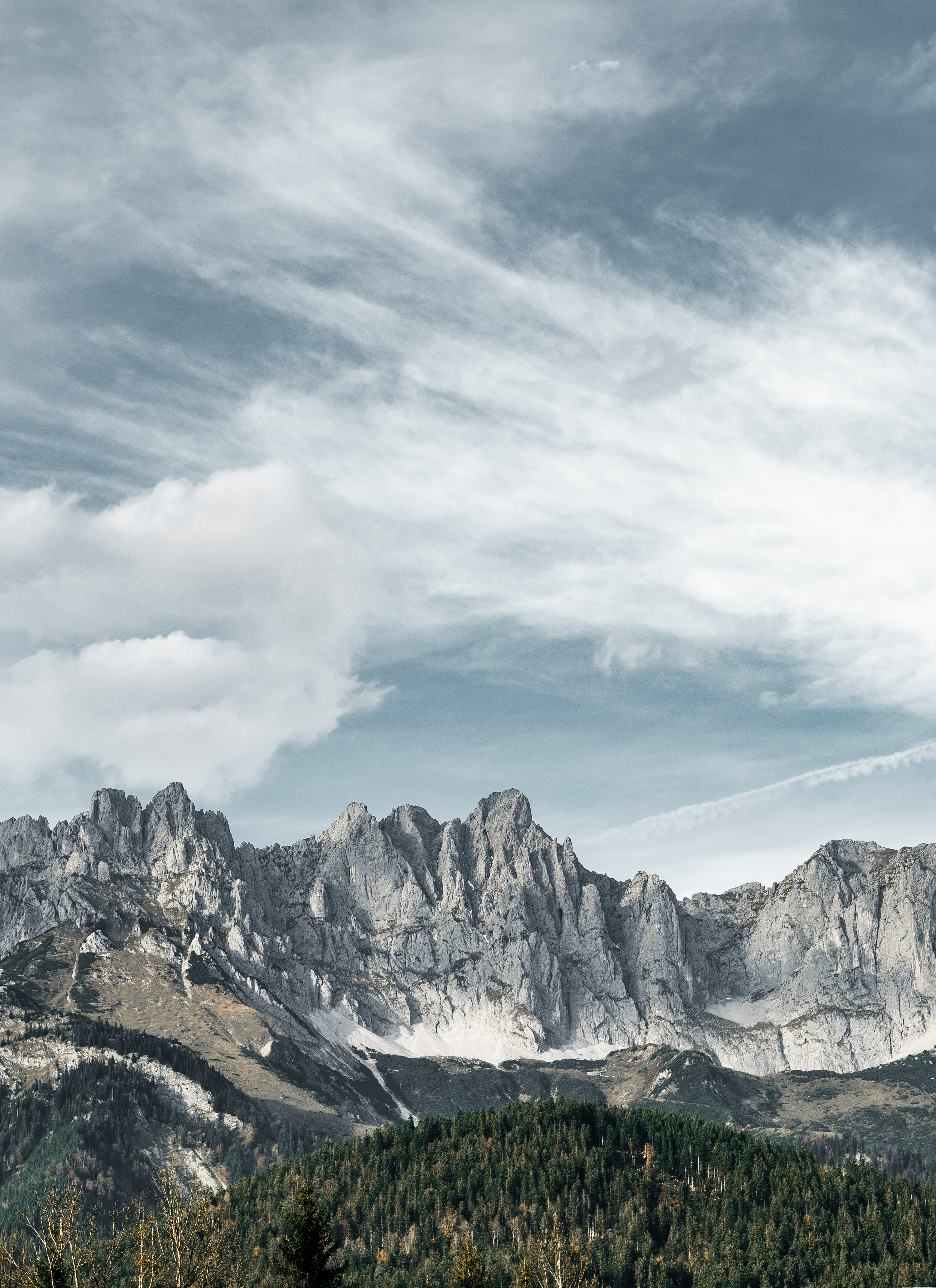 mountain near forest under clouds