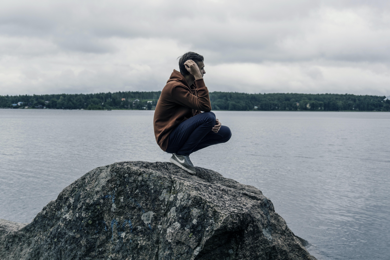 man wearing brown hoodie while standing on rock