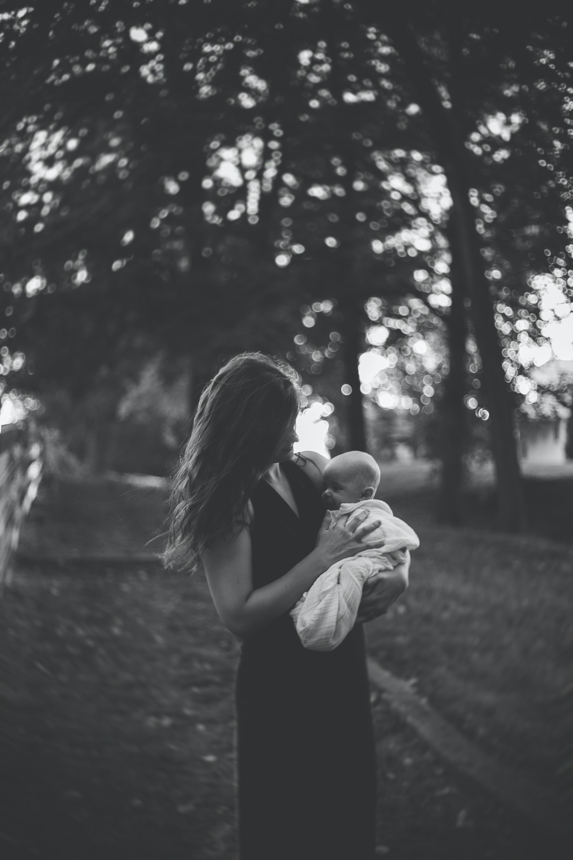 grayscale photography of woman carrying her child