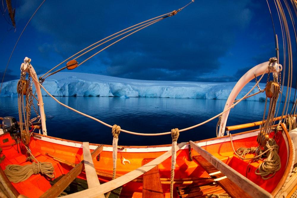fish-eye photograpy of fishing boat near ice glacier