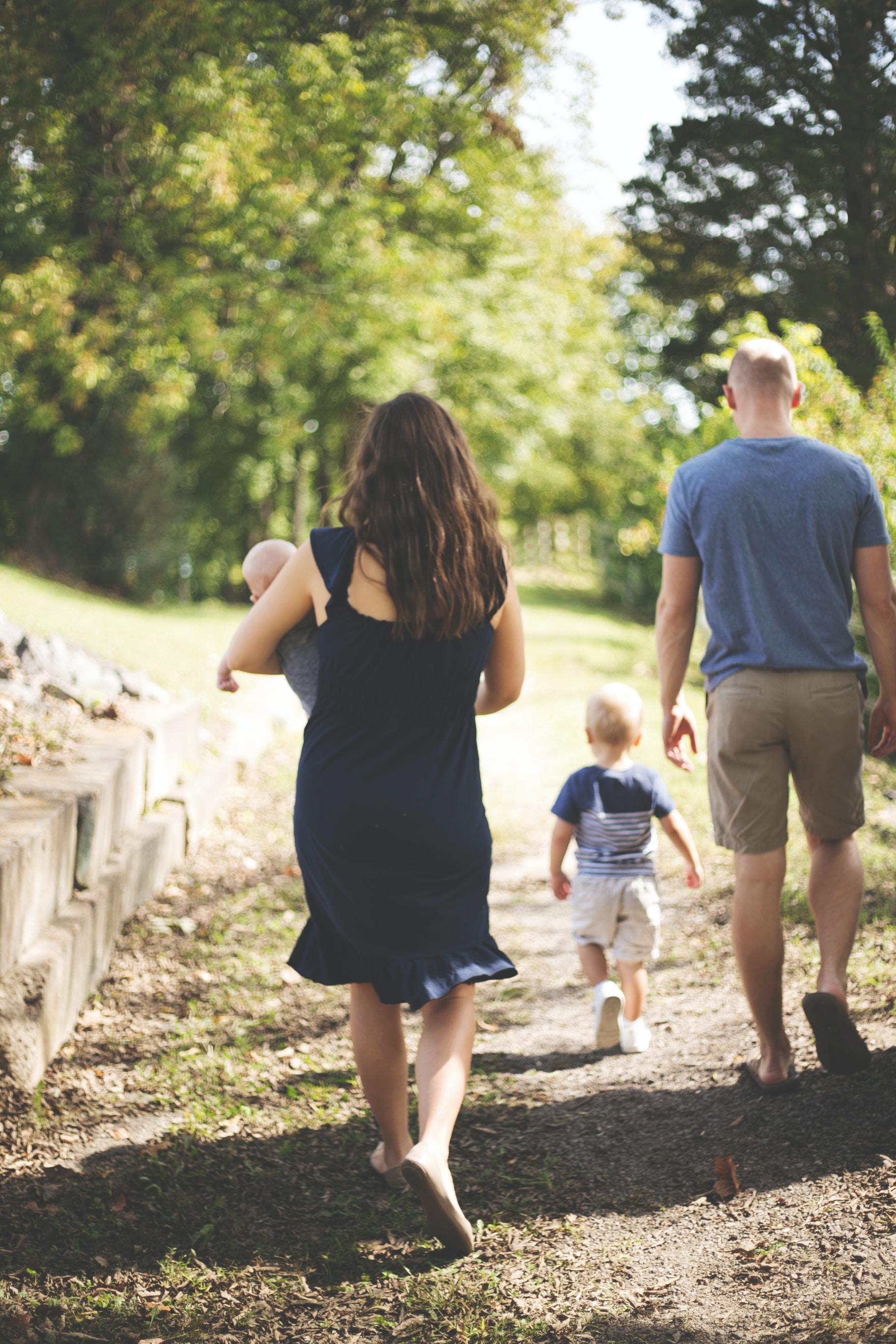 woman carrying baby near man