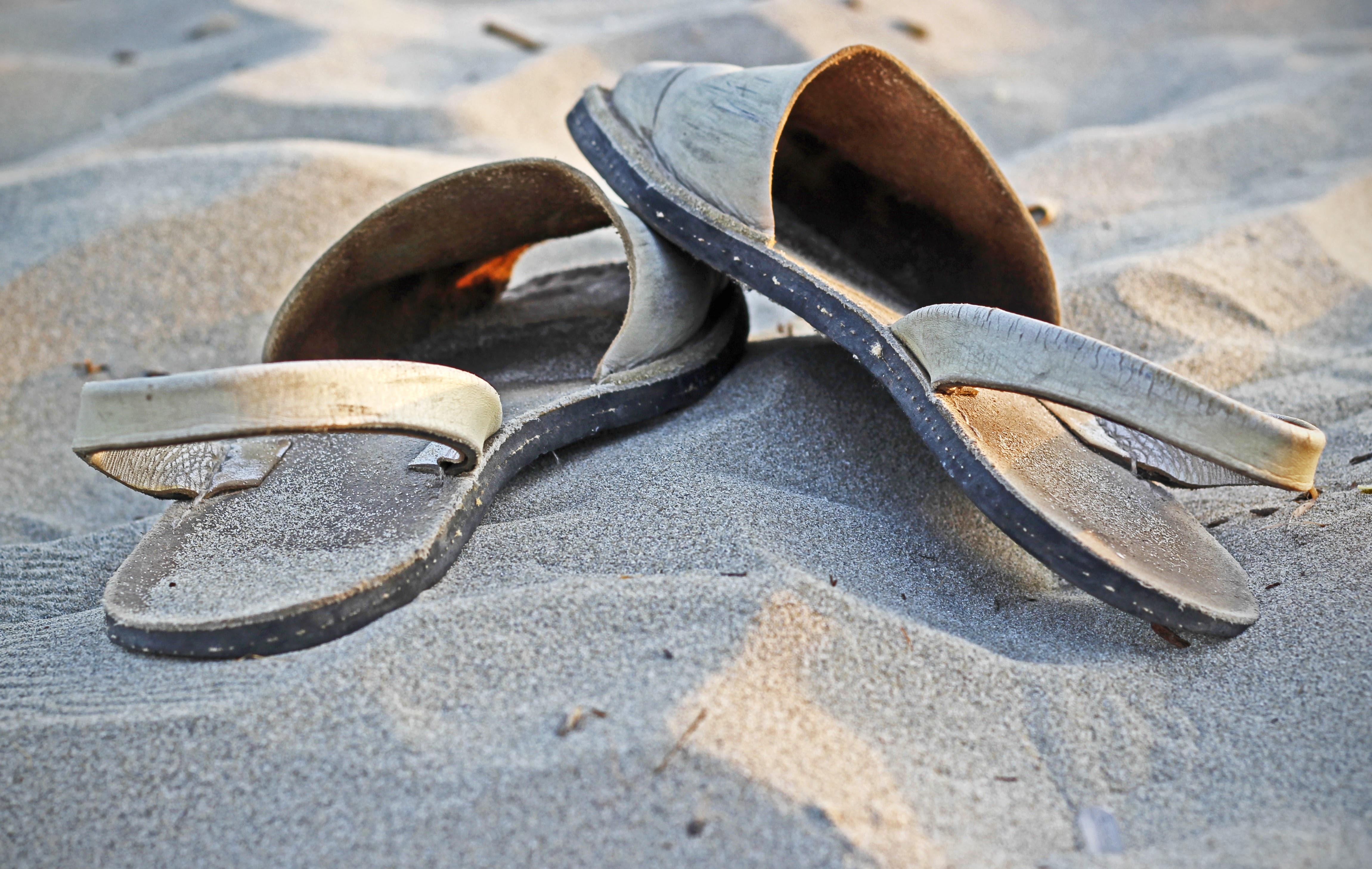 pair of beige sandals on sand
