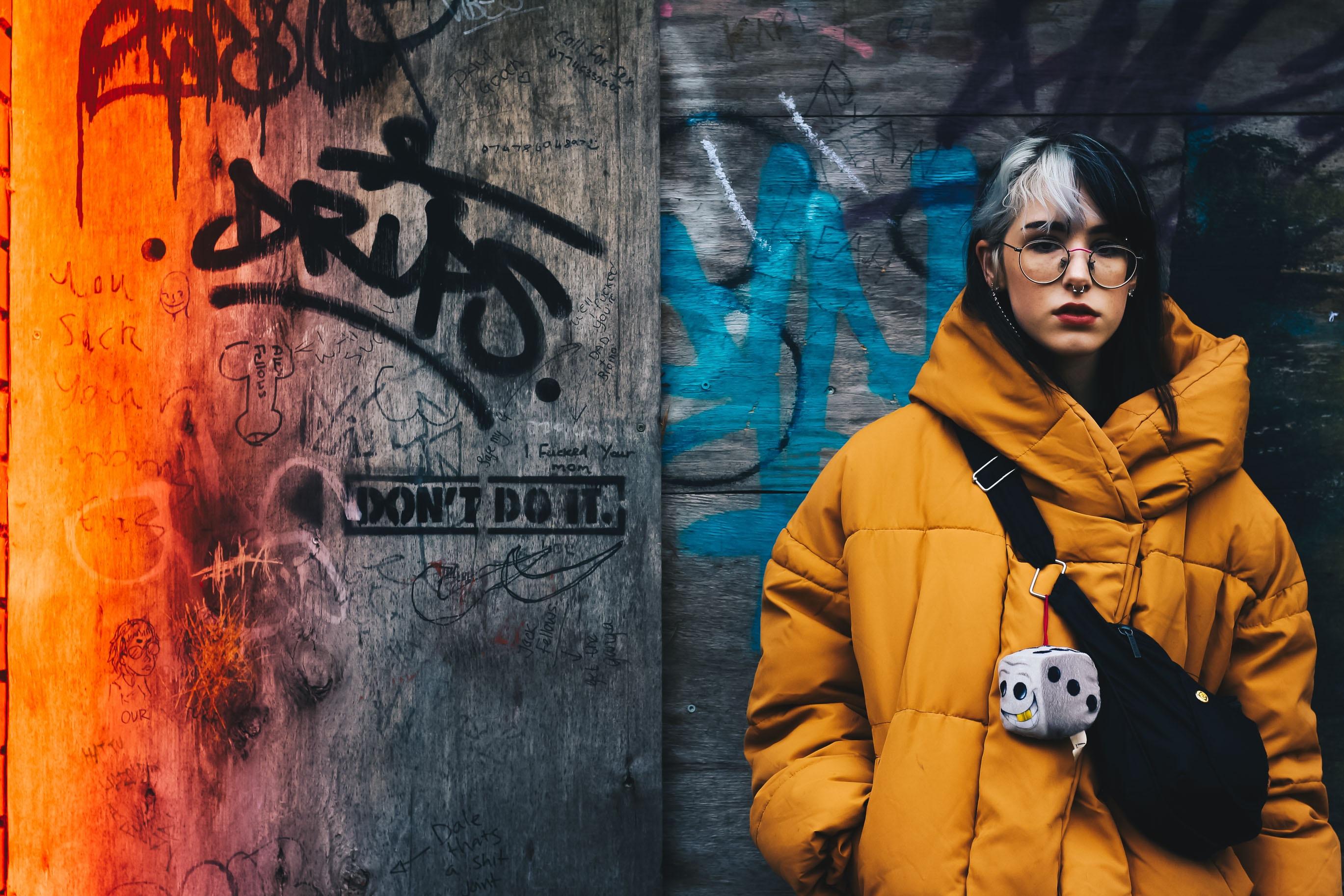 woman standing on gray graffiti wall