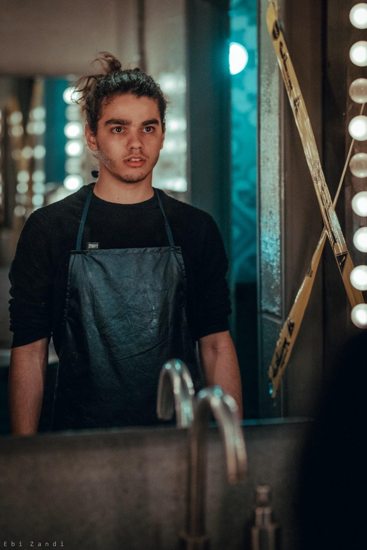 photo of man looking at mirror wearing black apron