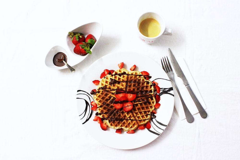 flat lay photo of waffle with strawberries on plate
