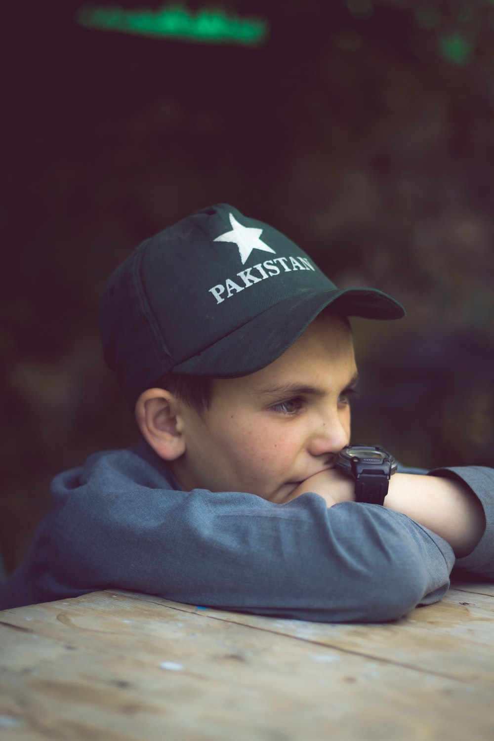 selective focus photography of boy leaning in front of brown wooden table