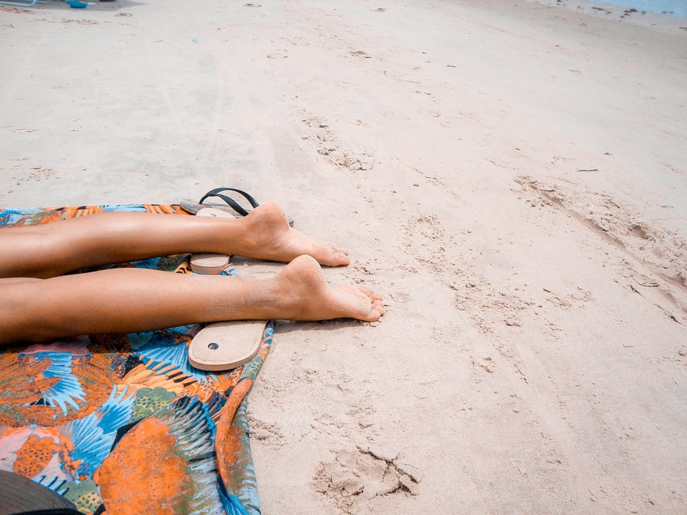 bare foot person lying on orange textile on brown sand during daytime
