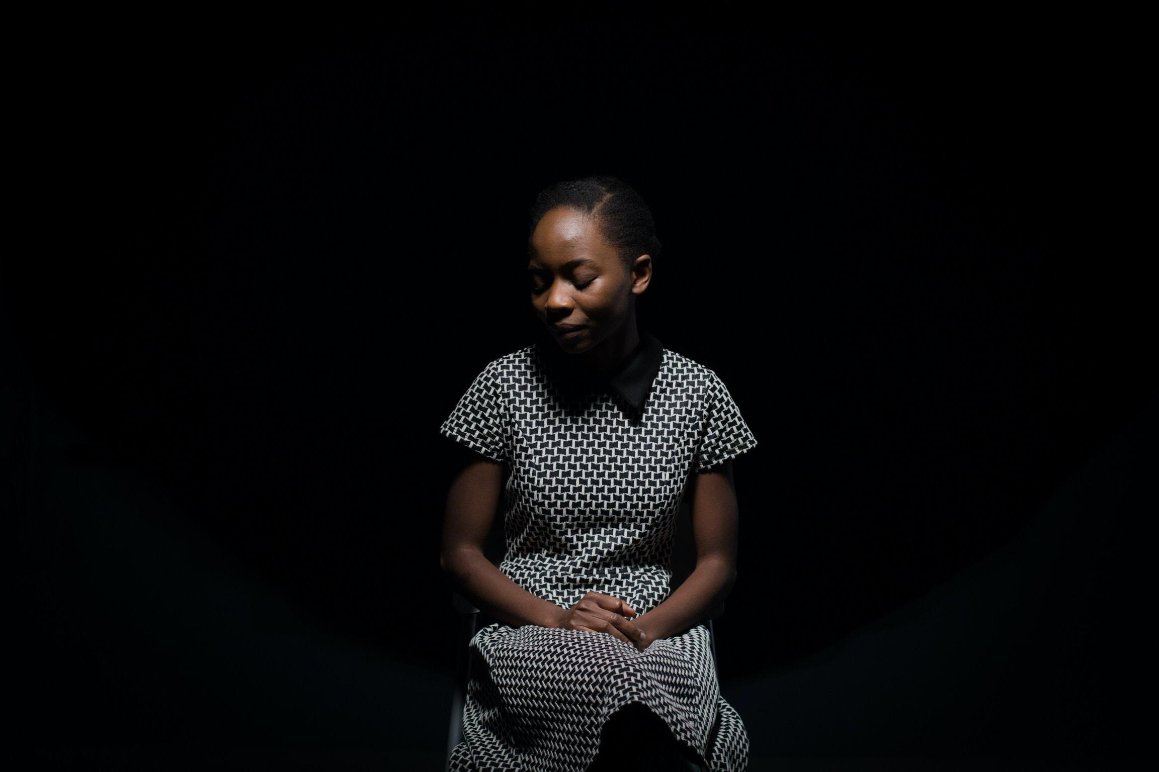 woman sitting on chair inside dark room