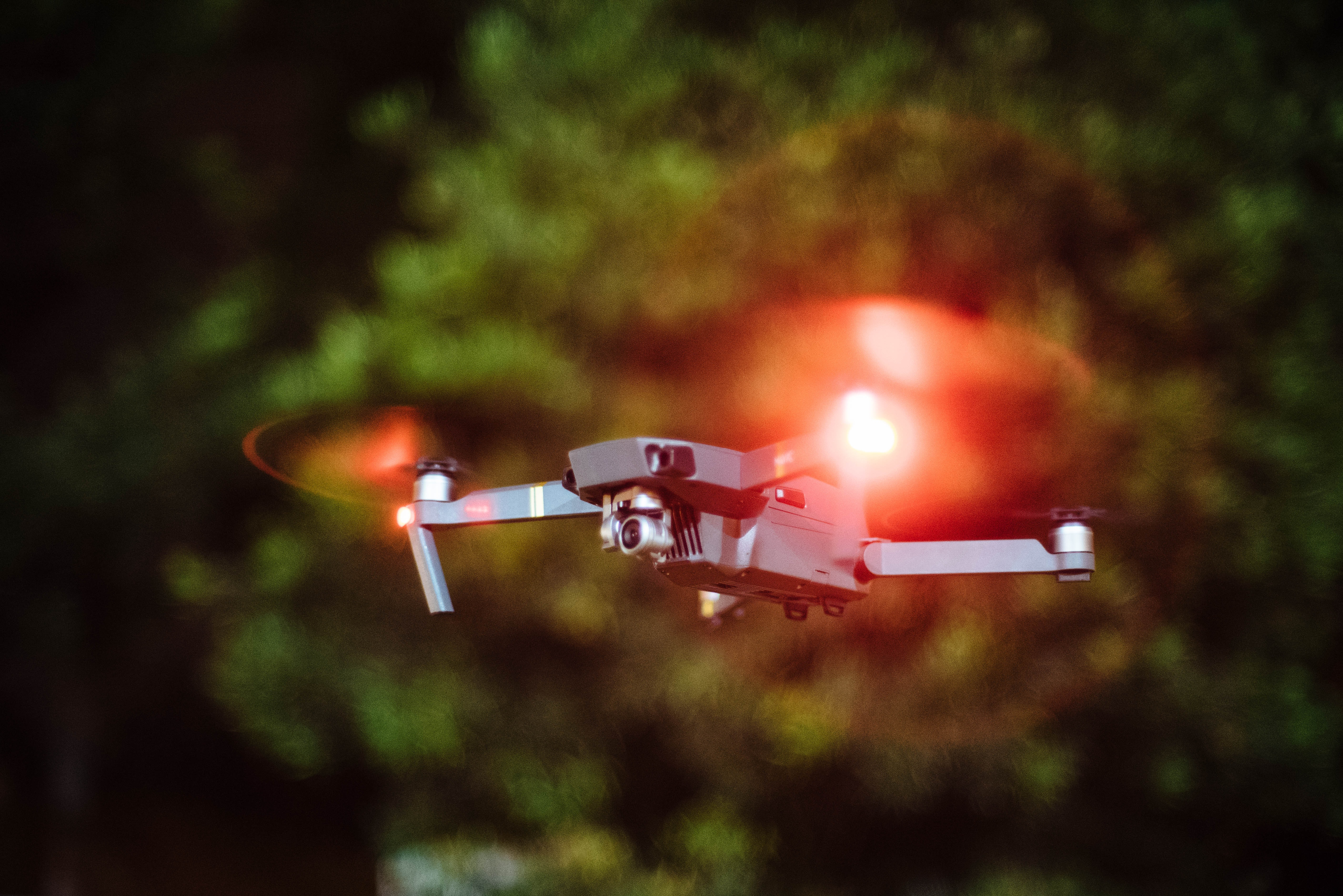 selective focus photography of drone flying on mid-air during nighttime