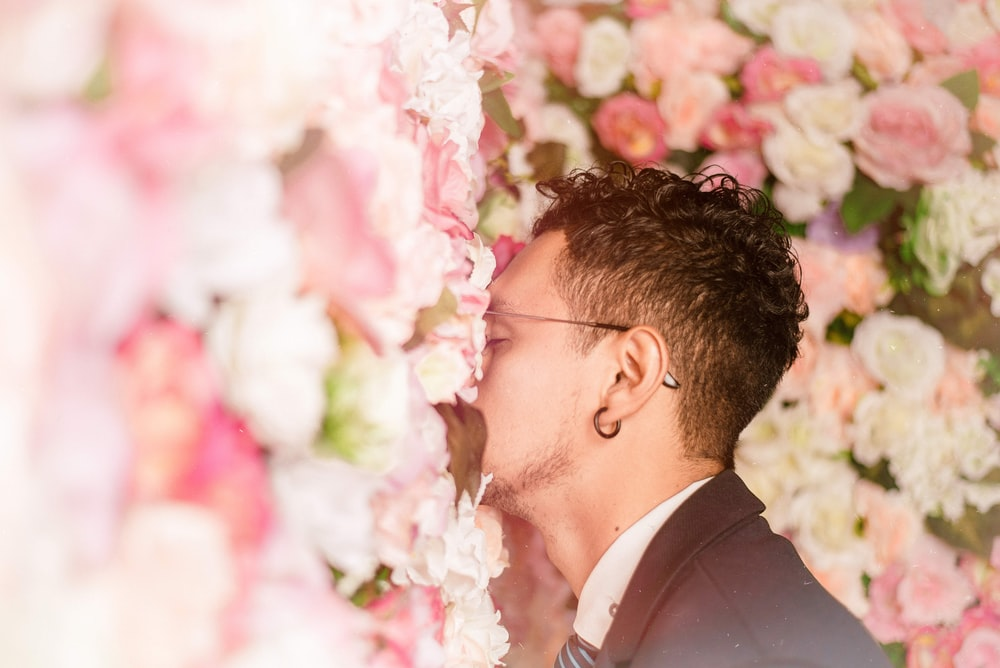 man leaning on flower wall