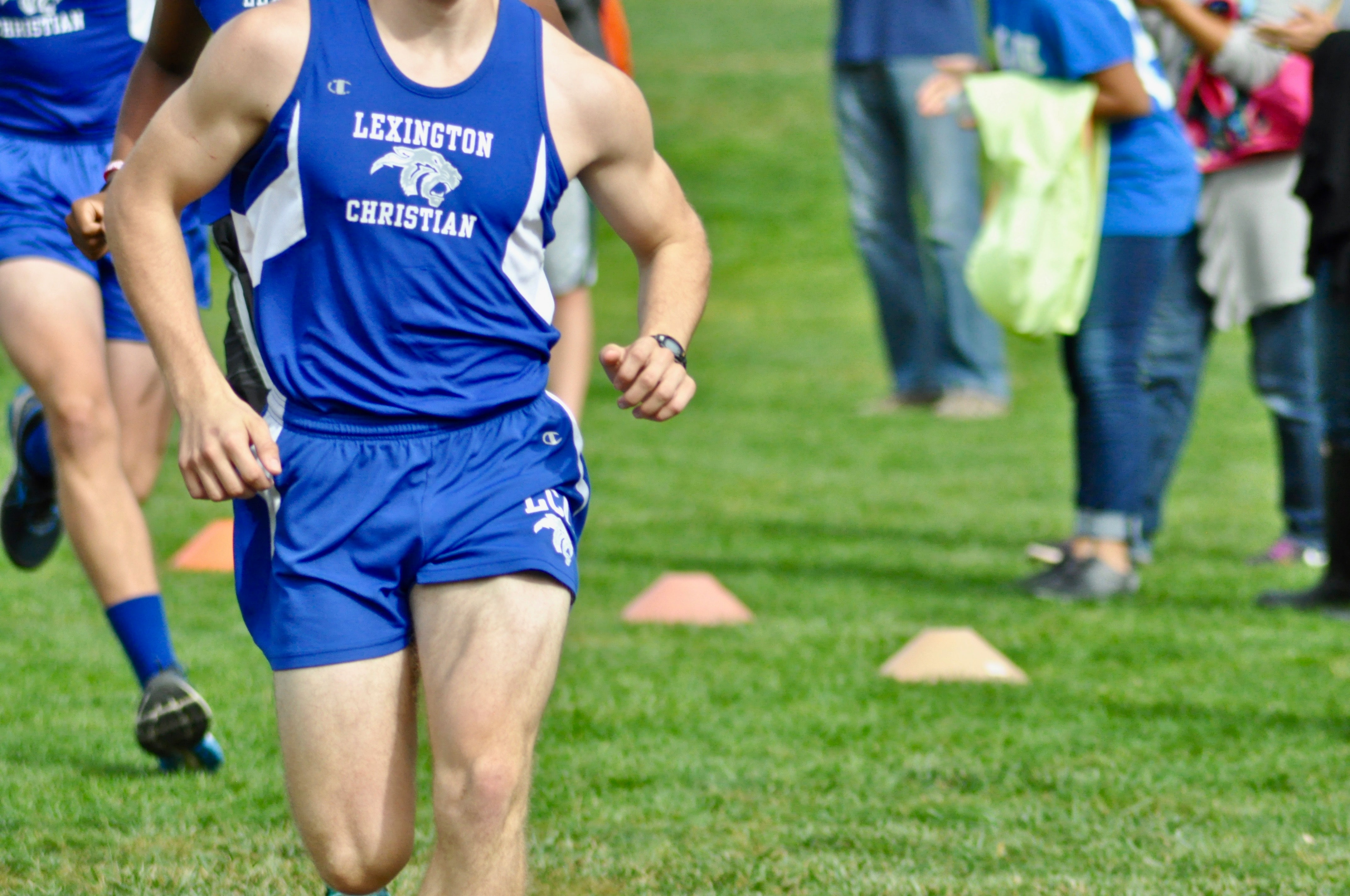 man in blue Champion tank top and shorts running at the field