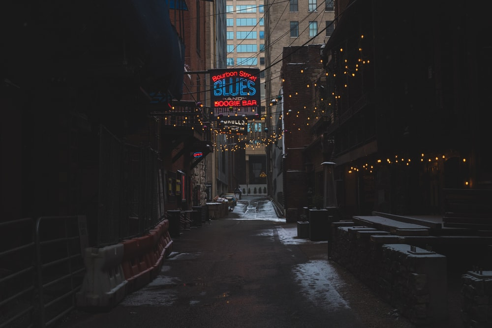 photography of Blues neon signage between buildings