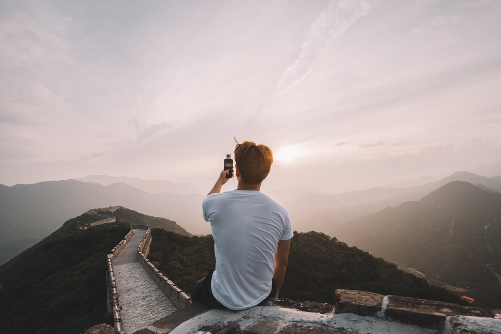 man sitting on cliff facing mountains