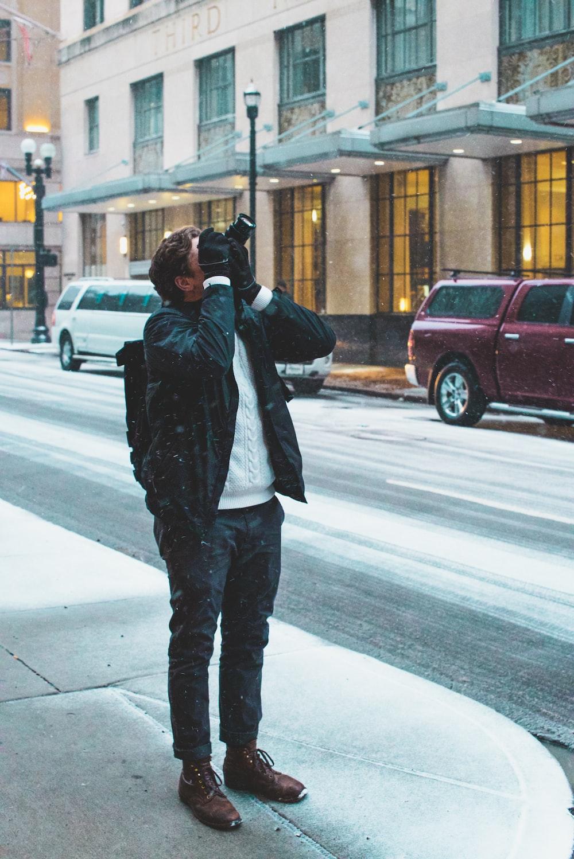 man standing on sidewalk holding DSLR camera taking picture above