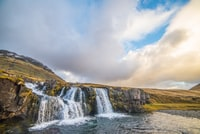waterfalls under blue clouds during daytime