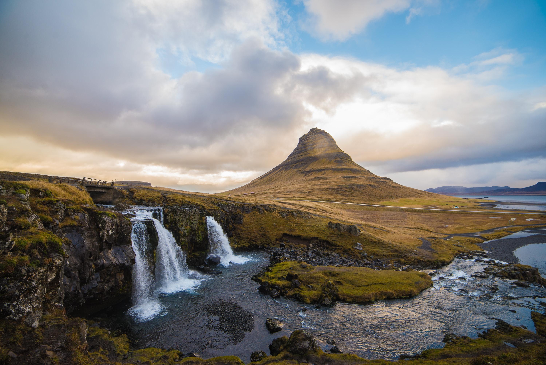 waterfall near brown hill under blue sky