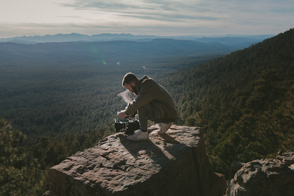 man sitting on top of mountain while holding DSLR camera